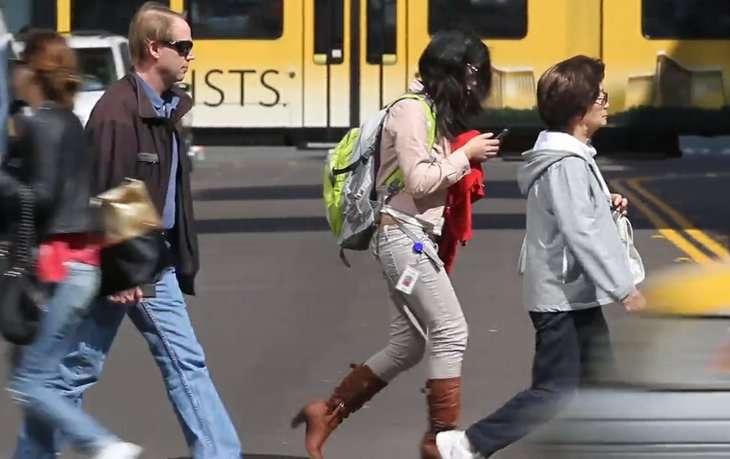 Woman on her phone jaywalking