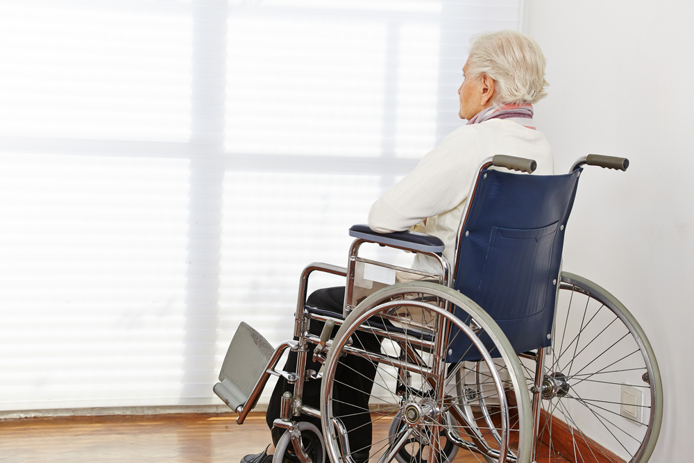 Elderly woman looking out a window while sitting in a wheelchair.