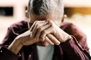 Elderly man covering his face, distraught.