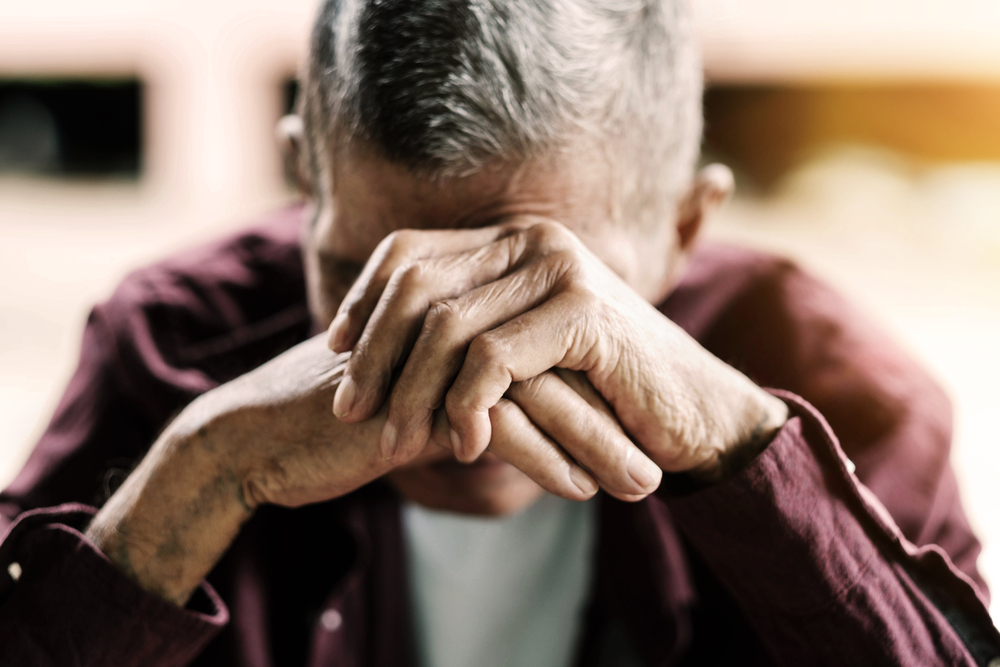 Depressed elderly man with head in his hands.